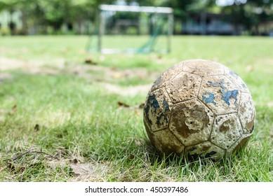 old soccer ball on green grass field