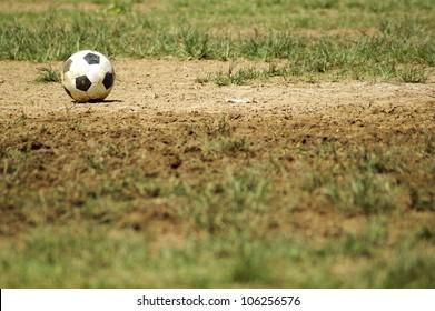 Old Soccer Ball. Poor school soccer field. Charity.