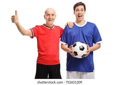 Old soccer player making a thumb up sign with a young soccer player holding a football isolated on white background