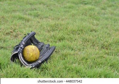 old sofball in old glove softball. glove softball on grass.