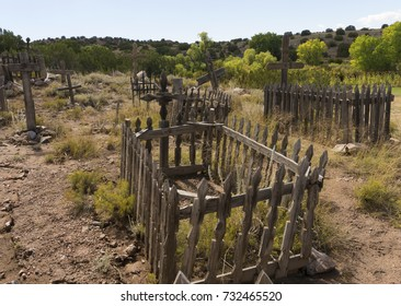 Old southwest graveyard with faded wood crosses and wooden picket fence grave markers in rocky landscape.