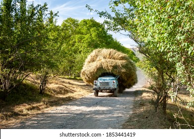 Old soviet truck full of hay. Tractor full with bale hay on village road near Sary Chelek lake, Sary-Chelek Jalal Abad region, Kyrgyzstan, Trekking in Central Asia. Peasant car rural agriculture.