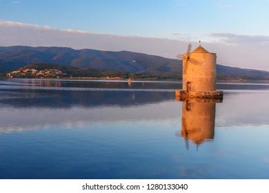 Old Spanish windmill in lagoon Orbetello on peninsula Argentario at sunise. Tuscany. Italy