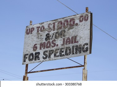 Old speeding sign on side of road.