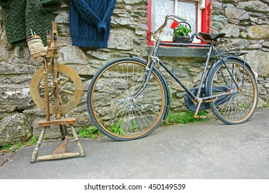 Old spinning wheel, woolen clothing and a rustic bike propped against the wall of an Irish cottage, The Ring of Kerry, Ireland