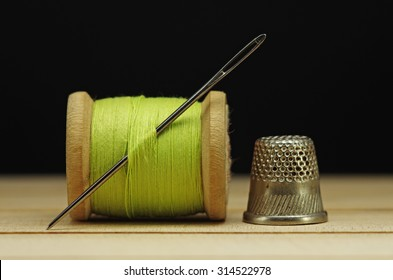 Old spool of thread with needle closeup. Tailor's work table. textile or fine cloth making.