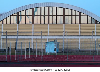 Old sports hall in winter light. In front of the hall a tennis court.  They all have been deconstructed nowadays.