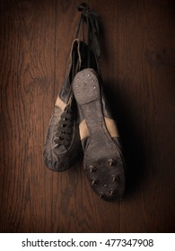 Old sports shoes from 1930 on a rustic wooden wall