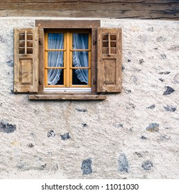 Old square wooden window with shutters in stone rendered wall of Swiss Alpine chalet