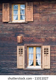 Old square wooden windows with shutters in wooden Swiss Alpine chalet