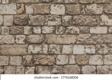 Old stable stone wall with rows of crafted masonry stones. Brickwork with individual craft bricks pattern. Strong manual work construction build has stability. Nice creativity vintage pattern