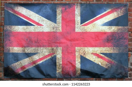 an old stained dirty union jack british flag with dark crumpled edges on a brick wall background