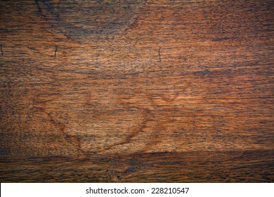 An old stained oak tabletop full of scratches and blemishes.