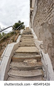 Old stairs with cracked, uneven concrete stairs goes up