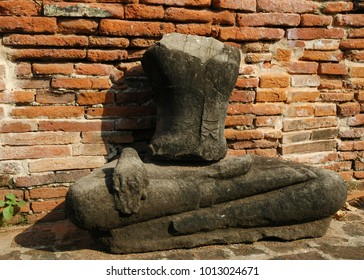 An old statue of a buddha rests in front of a brick wall. The statue lacks a head and and arms, and the feet are also missing. The red bricks are crumbling, with small plants growing between them.