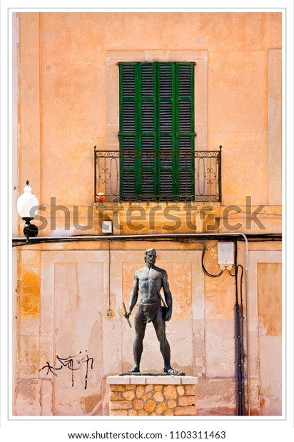 old statue stands guard outside an old textured building