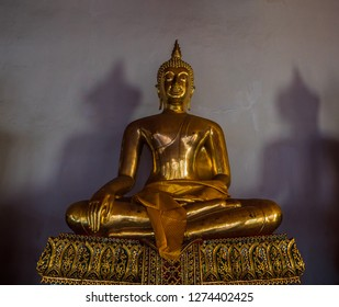 Old statue in Thailand. Fully gold plated. It's sitting in the middle of a room in front of the wall. The shadows spread on the wall.