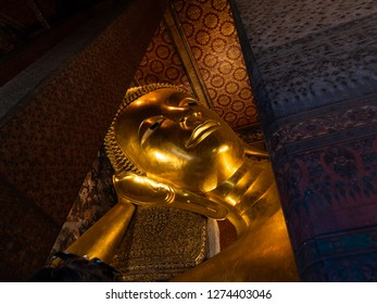 Old statue in Thailand. Fully gold plated. He's sitting in the middle of a room in front of the wall. The shadows spread on the wall.