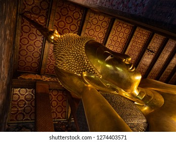 Old statue in Thailand. Fully gold plated. He is lying in the middle of a room in front of the wall. The shadows spread on the wall.
