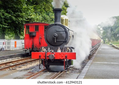 Old Steam locomotive on railroad station. Retro Red black steam train front on rail station. Vintage Steam railway road Isle of Man. Old Locomotive on station UK rail travel.Vintage UK train travel