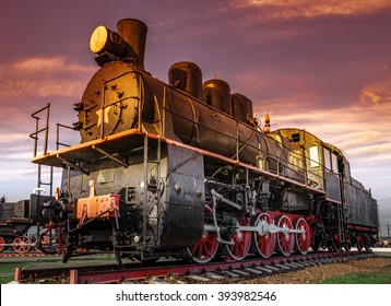 The old Old steam locomotive on sunset background. Vintage style train