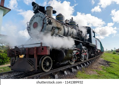 Old steam locomotive or railway train arriving to the platform of station.