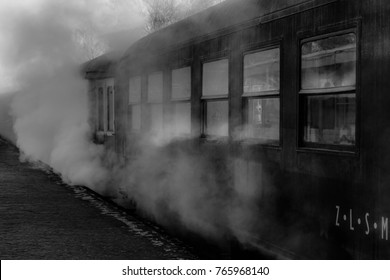 An old steam locomotive standing at the Simpelveld train station waiting for the passengers to enter the train. This picture was taken on a cold winter day making the steam even more impressive