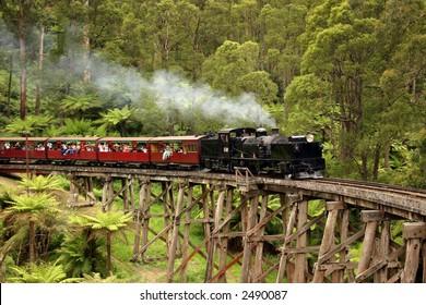 Old steam train crossing a bridge
