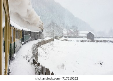 Old steam train in the middle of the winter running through snow abundance.