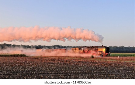 An old steam train with a nice smoke plum in the Netherlands in the early morning with beautiful sun light