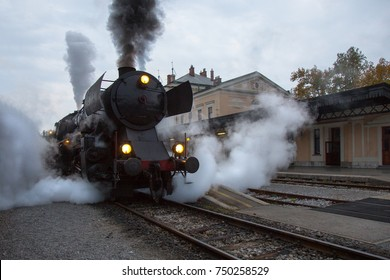 Old Steam train on Railway Station of Nova Gorica, Slovenia. Old Steam Locomotive of black color is driving and leaving a lot of smoke from chimney and vapour.