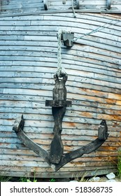 a old steel anchor at wooden background