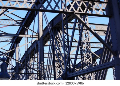 Old steel bridge-rivets and beams of black bridge-abstract closeup with blue sky as background