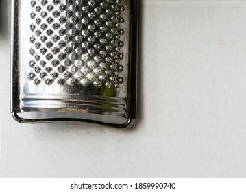 Old steel grater hanging on a tiled wall. Cooking utensils. Cheese grater