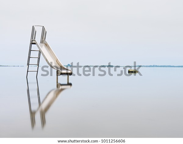 Old steel slide in lake. Chrome ladder tower with  sliding track, big granite stones around. Smooth water level and island at horizon. End of season in  natural swimming resort