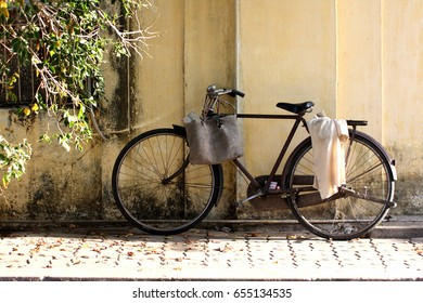 Old but still active bicycle parked against the wall with wooden basket and shirt