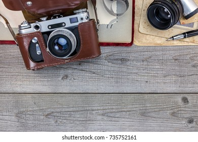 old still camera in leather case, photo album and old pictures on wooden background