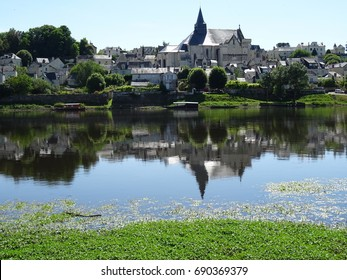 The old stone abbey and the village of Candes St Martin reflecting in the river in France on a hot summer day
