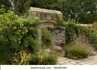 Old stone block wall and heavy wooden gate leading from a secret garden.