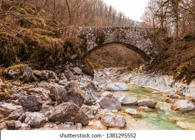 Old stone bridge across small stream in the woods.