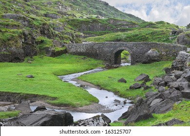 An old stone bridge carries a narrow road across the winding Serpent River in the rocky terrain near the Gap of Dunloe, famous tourist destination near Killarney, County Kerry, Ireland.