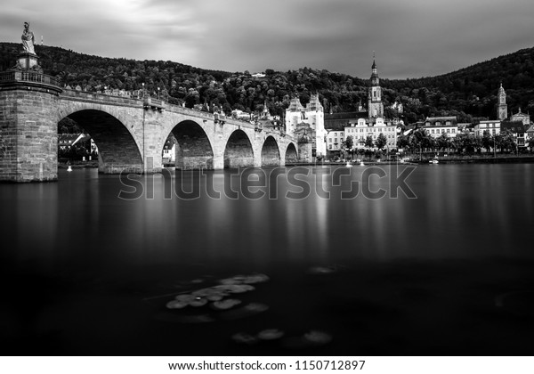 Old stone bridge during a rainy day crossing the river neckar with the old town of Heidelberg, Germany in the background