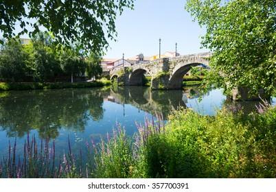 old stone bridge at Monforte de Lemos in sunny day. Galicia, Spain