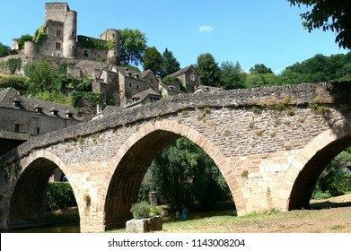Old stone bridge on the Aveyron river and medieval village of Belcastel; Aveyron, France