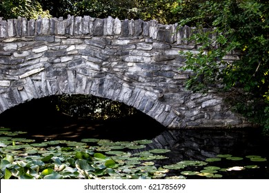 Old stone bridge over a lily pond