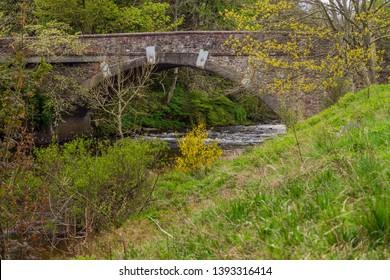 Old stone bridge over a the river isla running towards the Reekie Linn waterfall near Alyth, in Highland Perthshire, Scotland.