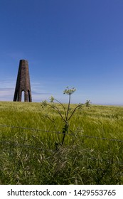 Old stone built navigational tower in a cereal field on the coast next to the sea in Devon