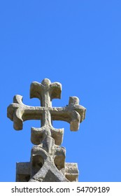 an old stone carved cross against a bright blue sky