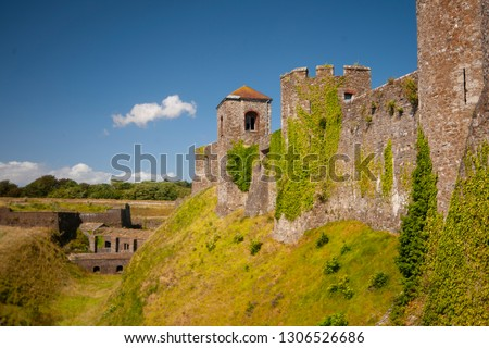 The old stone castle overgrown with greenery on the blue sky background