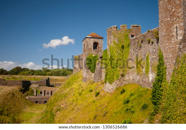 The old stone castle overgrown with greenery on the blue sky background.